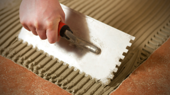 Hand holding a notched trowel tiling a floor