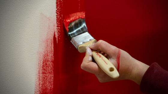 Hand holding a Purdy paintbrush painting a wall with red paint