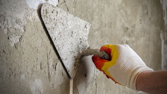 Hand holding a trowel plastering a wall